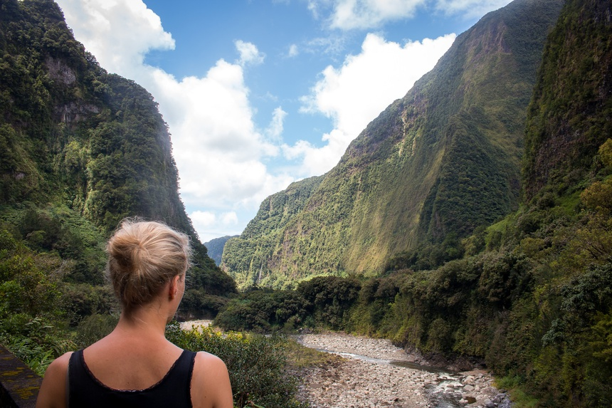 Ile de la Reunion blonde woman looking into a green mountain canyon and riverbed landscape