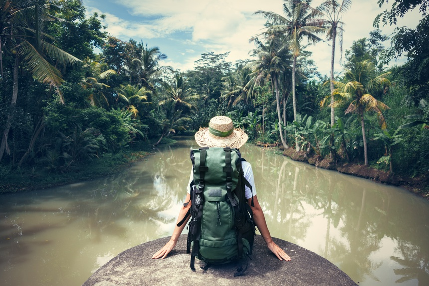 Woman traveler with backpack sitting on the edge and looking at tropical river (intentional vintage color)