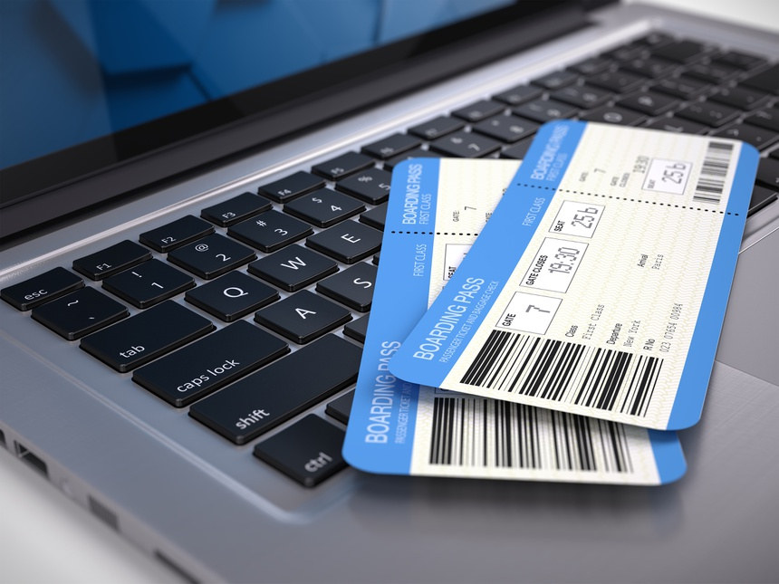 Two airline boarding pass tickets on laptop keyboard - online tickets booking concept