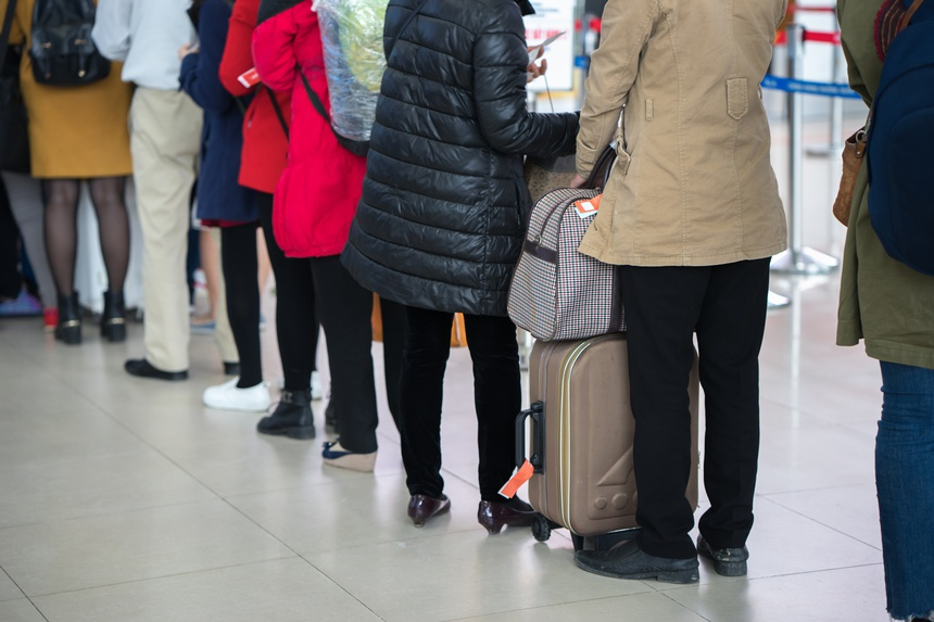 Queue of Asian people waiting at boarding gate at airport. Close