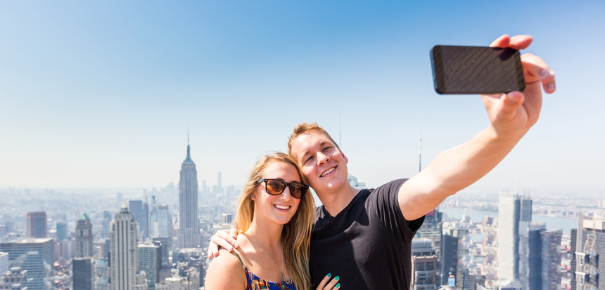 Young Couple Taking Selfie with New York on Background