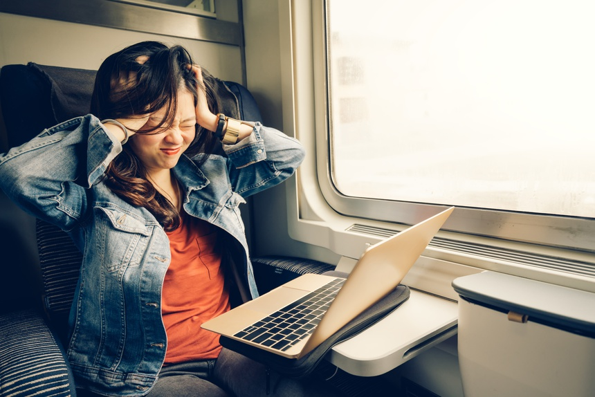 Asian college girl frustrated with laptop on the train, warm lig