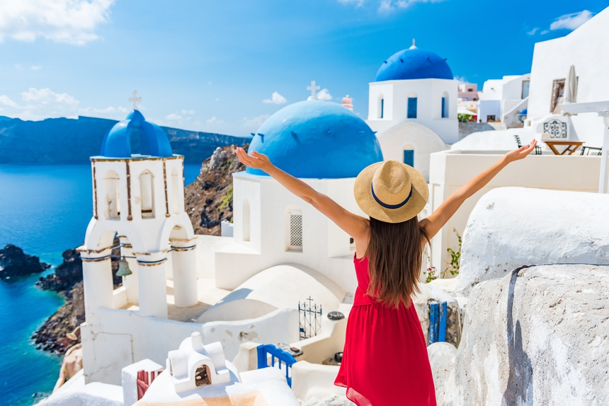 Europe travel happy vacation woman. Girl tourist having fun with open arms in freedom in Santorini cruise holiday, summer european destination. Red dress and hat person.
