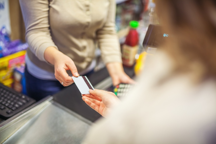 Woman paying with a credit card in a supermarket closeup