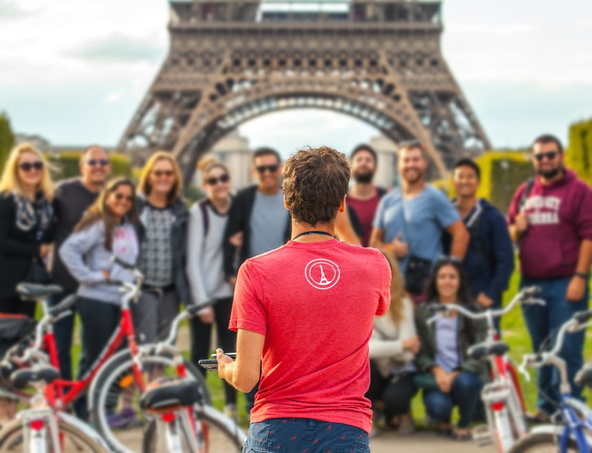 PARIS, FRANCE - AUGUST 30, 2015: Man photographs big group of tourists against Eiffel Tower in Paris. France.