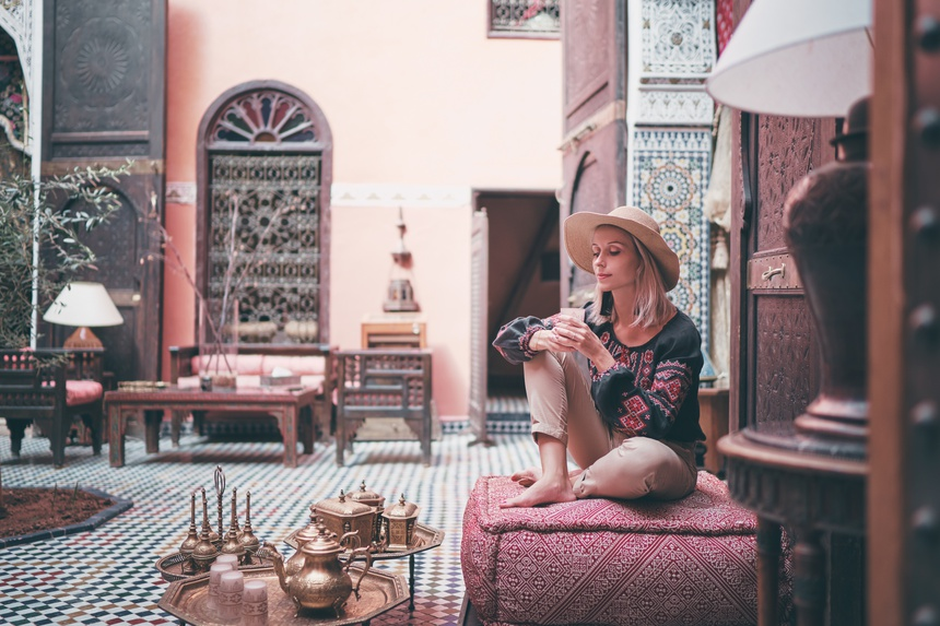 Traveling by Morocco. Happy young woman in hat relaxing in traditional riad interior in medina.