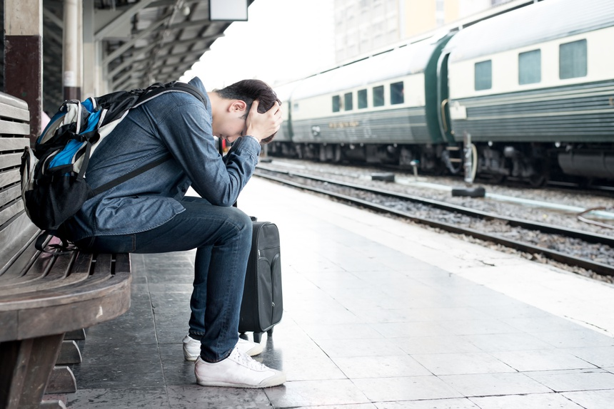Asian depressed traveler waiting at train station after mistakes