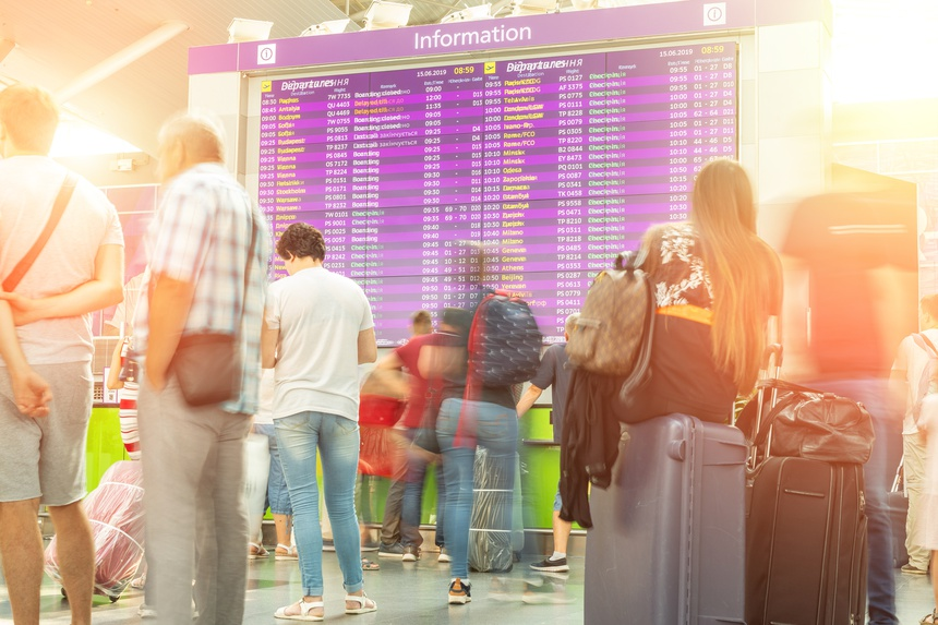 Motion blurred travellers crowd looking at fligh feparture and arrival timetable at airport terminal. Travel and tourism concept. Flight delay