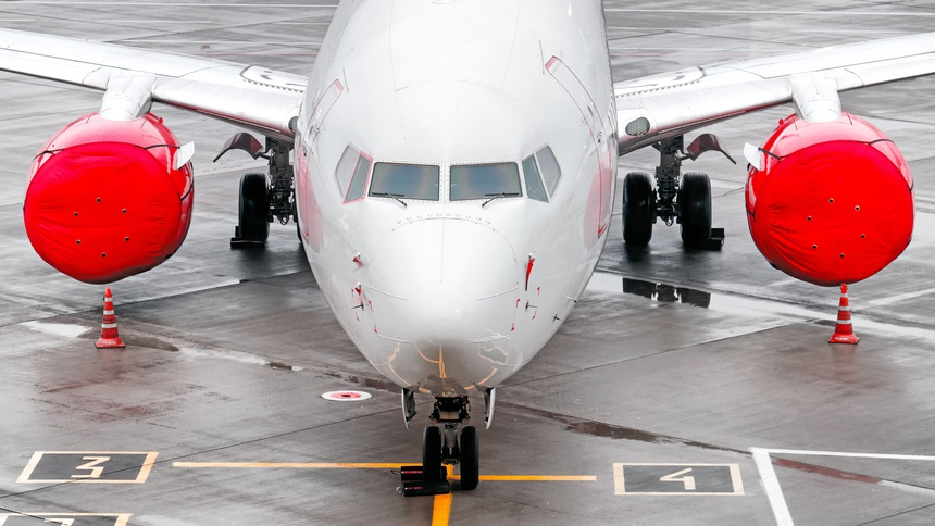 modern airplane on airport runway grounded with red jet plane engine against wet concrete apron background. Aerial top front closeup wide view of passenger aircraft on ground. Air travel banner