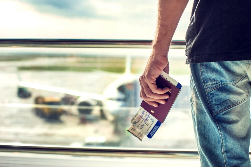 Closeup of man holding passports and boarding pass at airport. Traveling concept