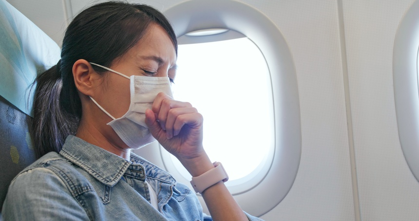 Woman feeling unwell and wearing face mask on plane