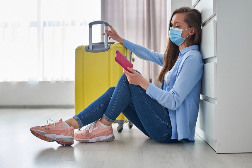 Woman traveler in medical protective mask affected by flight delay and cancelled travel and vacation. Travel ban and troubles due to coronavirus outbreak and covid ncov virus epidemic