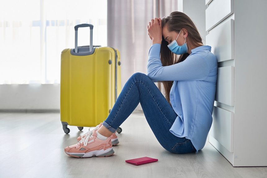Frustrated woman traveler in protective mask affected by flight delay and cancelled travel and vacation. Travel ban and problems due to coronavirus outbreak and covid ncov virus epidemic