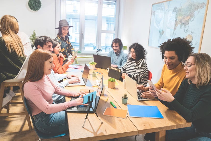 Young co-workers team talking during startup - Happy people planning a new project in creative coworking office - Technology, entrepreneur, marketing concept - Focus on left girl face with red hair