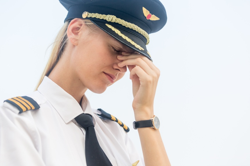 Sleepless tired young female pilot in uniform with her hand on her face. Sad and stressed. Unemployment and depression concept.