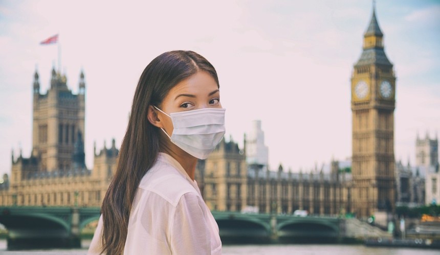 Corona virus travel corona virus spread prevention asian woman tourist wearing protective face mask on UK London city sightseeing holiday vacation. Famous british landmark background panoramic.