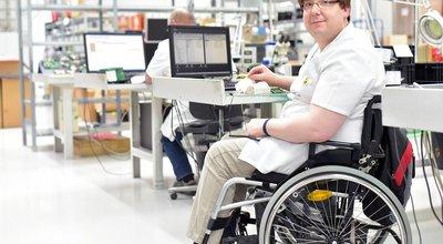 Rollstuhlfahrer am Arbeitsplatz in einer Fabrik zur Montage von Elektronik - Alltag mit Gehbehinderung // Wheelchair driver at the workplace in the industry