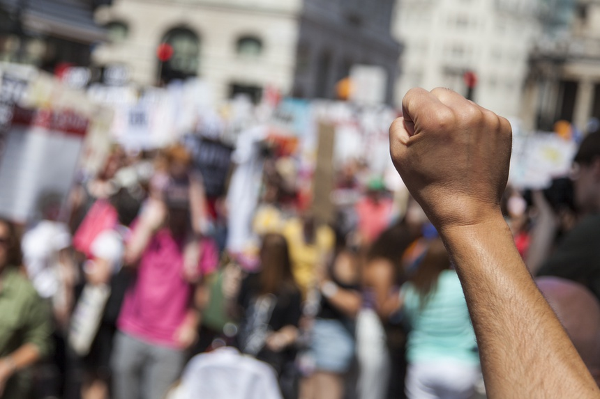 A raised fist of a protestor at a political demonstration