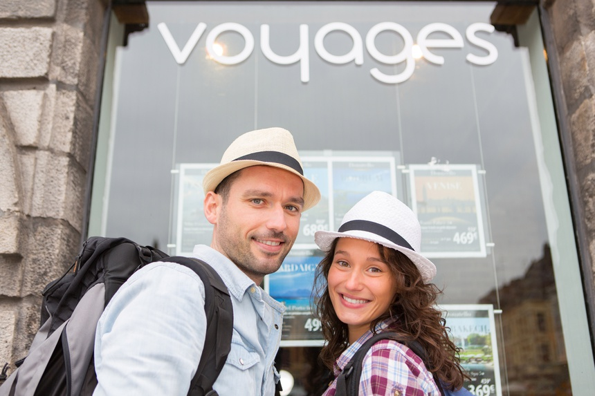 Young happy couple in front of travel agency