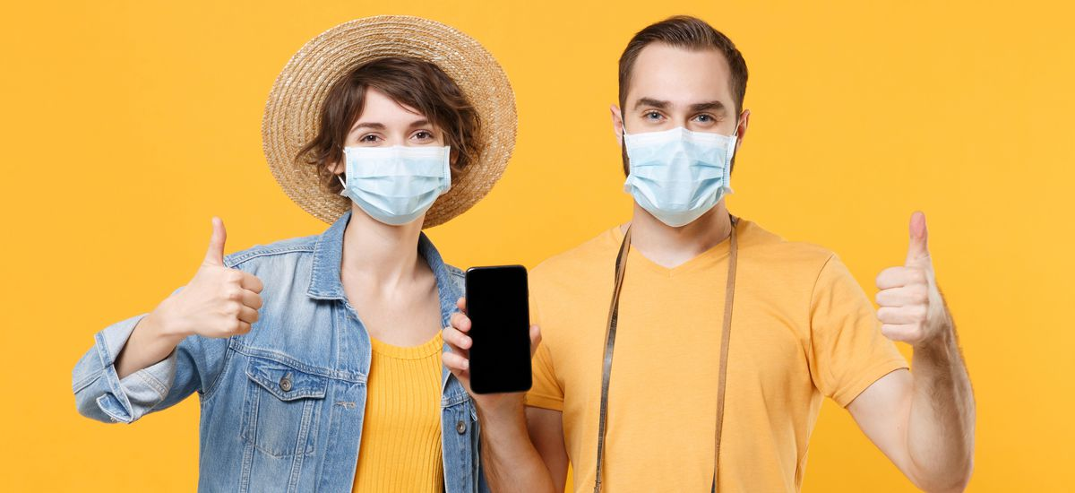 Tourists couple friends guy girl in face mask isolated on yellow background. Epidemic pandemic coronavirus 2019-ncov covid-19 flu virus concept. Hold mobile phone with blank screen showing thumbs up.