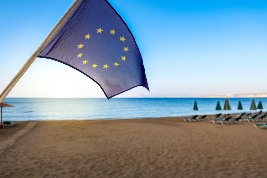 European Union EU flag with beach and sea in the background. Concept for traveling and tourism in Europe.