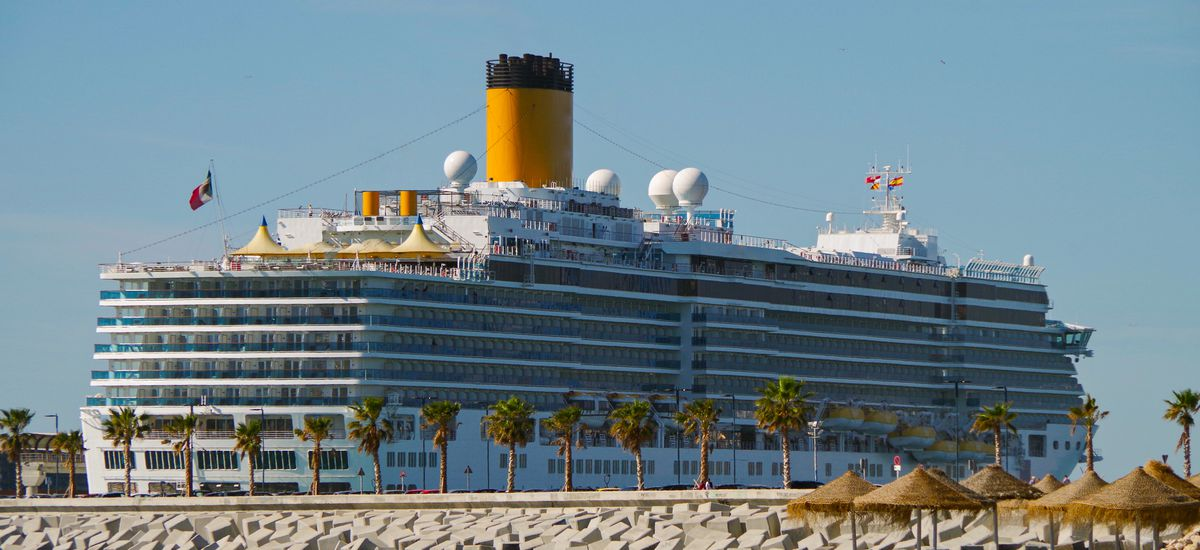 Costa Cruises cruise ship or cruiseship liner Costa Deliziosa in port of Malaga with with sandy beach and palm trees in the Mediterranean