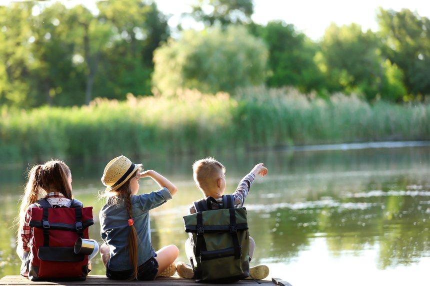 Little children sitting on wooden pier. Summer camp