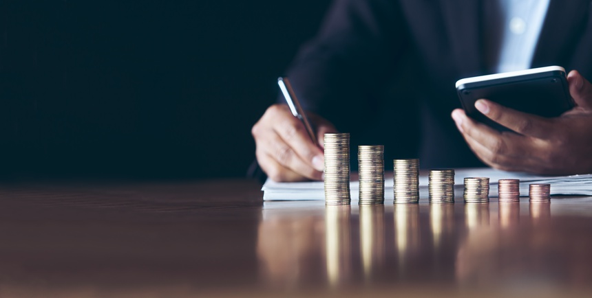 businessmen use calculators with placing coins in a growing position,Investment concepts, financial growth and saving