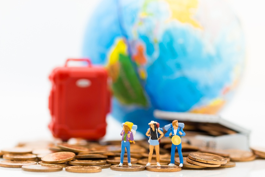 Miniature people : Travelers stand on a pile of coins and have a red suitcase, world map for background. Image use for travel, business concept.