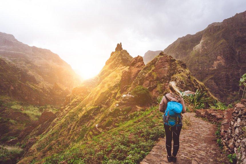 Girl walking down along the trekking route to verdant Xo-Xo valley. Warm sunlight seable on horizont. Santo Antao Island Cape Verde