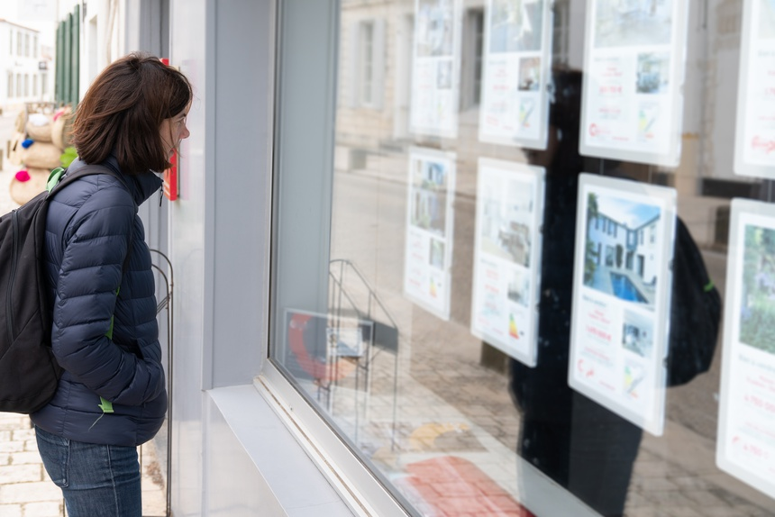 woman in front of the window of a real estate agency