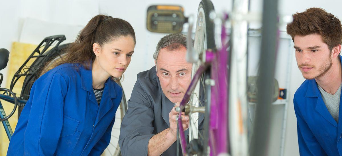young woman and man repairing bicycle wheel