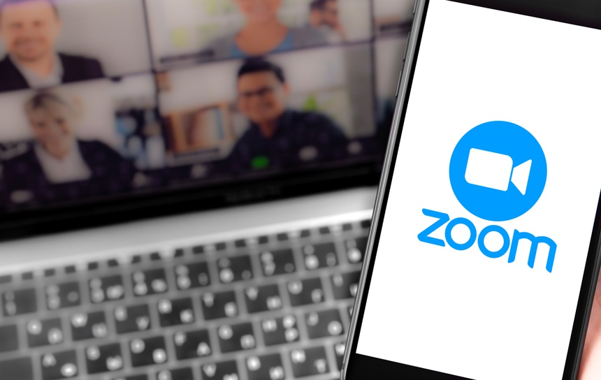Zoom logo on the screen smartphone and notebook background closeup. Zoom Video Communications is a company that provides remote conferencing services. Moscow, Russia - April 1, 2020