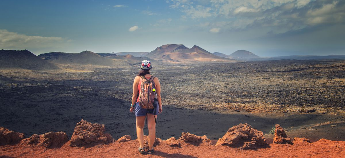 The tourist is standing on the edge of the rock and looks at the red mountains in the national park Timanfaya in Lanzarote
