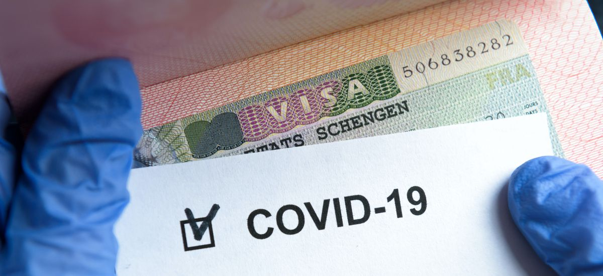 COVID-19 coronavirus pandemic and travel concept, positive mark COVID-19 and Schengen Visa stamp. Passport control of tourists with coronavirus check.