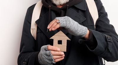 unrecognizable old man wearing street clothes holding house made of cardboard, dream about shelter. Isolated over white background