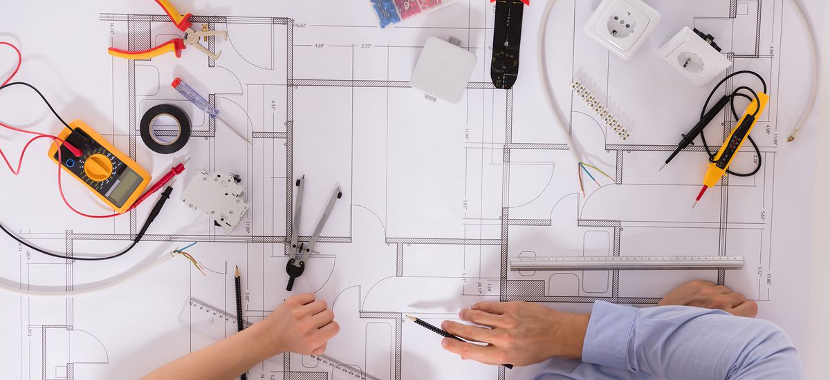 Elevated View Of Architect's Hand On Blueprint