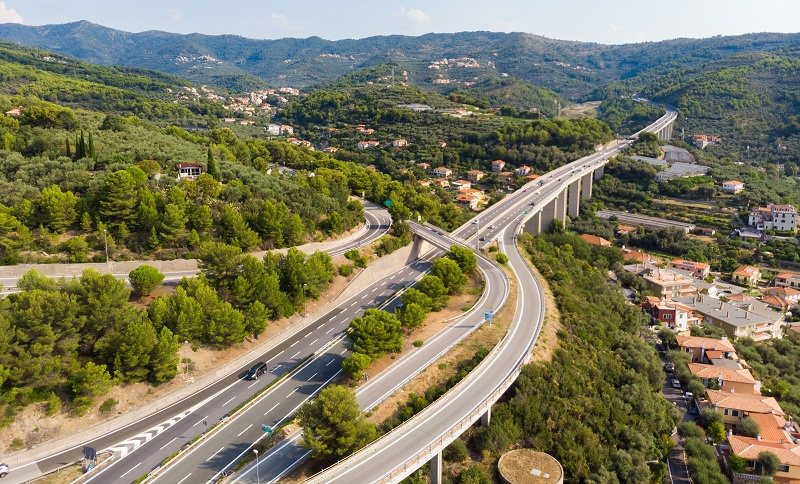Aerial view of multiple lane highway crossing villages and forest hills (Autostrada dei Fiori - A10) Liguria Italy